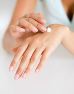Close up image of a woman applying a small amount of white cream to her hand